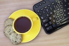 Ένα φλυτζάνι του τσαγιού πρωινού με τα μπισκότα δίπλα στο πληκτρολόγιο Στοκ Φωτογραφία