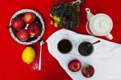 Ένα φλυτζάνι του τσαγιού, του λεμονιού σε ένα κόκκινο υπόβαθρο, των τροφίμων και του ποτού, του μαχαιριού και του δικράνου, χρόνο Στοκ εικόνες με δικαίωμα ελεύθερης χρήσης