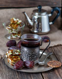 Ένα φλυτζάνι του τσαγιού, των γλασαρισμένων ψημένων καρυδιών και των ημερομηνιών στον πίνακα του θορίου Στοκ Εικόνες
