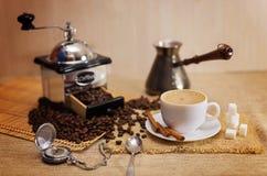 Ένα φλυτζάνι του φυσικού καφέ, φασόλια καφέ, Arabica, ραβδί κανέλας Στοκ Εικόνες