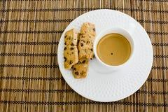 Ένα φλυτζάνι των άσπρων μπισκότων τσιπ καφέ και σοκολάτας άνω του ξύλινου τ Στοκ Εικόνες