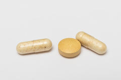 Ένα χάπι και σκληρές κάψες στο άσπρο υπόβαθρο Στοκ Φωτογραφία