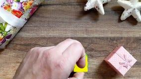 Ένα χέρι ατόμων ` s διαμορφώνει τα Χριστούγεννα λέξης σε έναν ξύλινο πίνακα με τις διακοσμήσεις Χριστουγέννων απόθεμα βίντεο