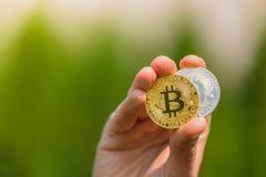 Ένα χέρι ατόμων ` s κρατά ένα χρυσό και ασημένιο νόμισμα bitcoin Στοκ φωτογραφία με δικαίωμα ελεύθερης χρήσης