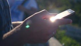 Ένα χέρι ατόμων ` s με ένα τηλέφωνο στο χέρι του, το οποίο πιάνει τις ακτίνες του ήλιου και των λάμψεων στη κάμερα HD, 1920x1080 απόθεμα βίντεο