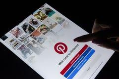 Ένα χέρι γυναικών ` s αγγίζει τη Apple iPad υπέρ τη νύχτα με την υπηρεσία Pinterest Διαδικτύου στην οθόνη Εφαρμογή Pinterest στην Στοκ εικόνα με δικαίωμα ελεύθερης χρήσης