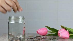Ένα χέρι γυναικών ` s παίρνει ένα νόμισμα σε ένα βάζο απόθεμα βίντεο