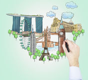 Ένα χέρι επισύρει την προσοχή τα σκίτσα των διασημότερων τουριστικών θέσεων στο ανοικτό πράσινο υπόβαθρο Η έννοια του τουρισμού κ Στοκ Εικόνες