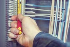 Ένα χέρι ηλεκτρολόγων κινηματογραφήσεων σε πρώτο πλάνο εκτελεί την ηλεκτρολογική εργασία Στοκ φωτογραφία με δικαίωμα ελεύθερης χρήσης