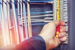 Ένα χέρι ηλεκτρολόγων κινηματογραφήσεων σε πρώτο πλάνο εκτελεί την ηλεκτρολογική εργασία Στοκ Εικόνα