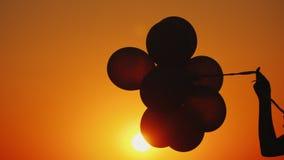 Ένα χέρι κρατά διάφορα μπαλόνια στο ηλιοβασίλεμα απόθεμα βίντεο