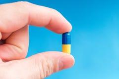 Ένα χέρι κρατά ένα μπλε-κίτρινο χάπι καψών σε ένα μπλε υπόβαθρο Στοκ φωτογραφίες με δικαίωμα ελεύθερης χρήσης