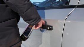 Ένα χέρι με ένα μπουκάλι του οινοπνεύματος ανοίγει την πόρτα του αυτοκινήτου απόθεμα βίντεο