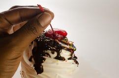 Ένα χέρι που κρατά έναν cherrry επάνω από το τεράστιο κέικ φλυτζανιών Στοκ φωτογραφίες με δικαίωμα ελεύθερης χρήσης