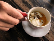 Ένα χέρι που κρατά ένα φλυτζάνι του μαλακός-βρασμένου αυγού στον ξύλινο πίνακα Στοκ φωτογραφία με δικαίωμα ελεύθερης χρήσης