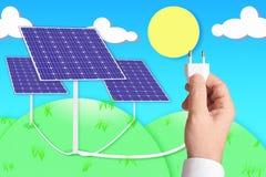 Ένα χέρι που κρατά ένα βούλωμα σύνδεσε με μερικές ηλιακές φωτοβολταϊκές επιτροπές Στοκ φωτογραφία με δικαίωμα ελεύθερης χρήσης