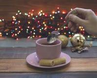 Ένα χέρι που κρατά ένα κουταλάκι του γλυκού, ένα φλυτζάνι του τσαγιού με το πιατάκι, παιχνίδια Χριστούγεννο-δέντρων Στοκ φωτογραφίες με δικαίωμα ελεύθερης χρήσης