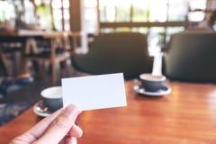 Ένα χέρι που κρατά την άσπρη κενή επαγγελματική κάρτα με δύο φλυτζάνια καφέ στον ξύλινο πίνακα στοκ εικόνα με δικαίωμα ελεύθερης χρήσης