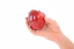 Ένα χέρι που κρατά την κόκκινη Apple στο λευκό Στοκ εικόνες με δικαίωμα ελεύθερης χρήσης