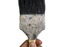Ένα χέρι που κρατά την παλαιά βρώμικη βούρτσα χρωμάτων στοκ εικόνα