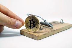 Ένα χέρι που παίρνει ένα νόμισμα του bitcoin από την ποντικοπαγήδα Στοκ Εικόνες