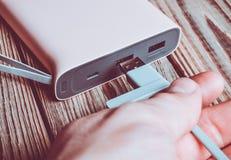 Ένα χέρι συνδέει ένα καλώδιο usb με μια τράπεζα δύναμης σε έναν ξύλινο στοκ φωτογραφία με δικαίωμα ελεύθερης χρήσης