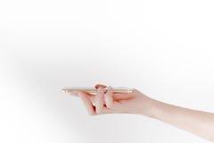 Ένα χέρι φέρνει το smartphone στο άσπρο υπόβαθρο στοκ εικόνα με δικαίωμα ελεύθερης χρήσης