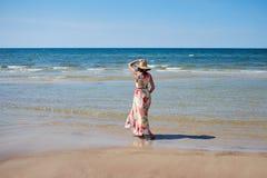 Ένα χαλαρωμένο κορίτσι με ένα καπέλο πηγαίνει κατά μήκος της παραλίας στοκ εικόνα