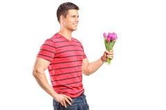 Ένα χαμογελώντας άτομο που κρατά μια δέσμη των λουλουδιών Στοκ Εικόνες