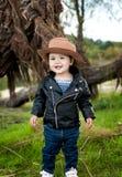 Ένα χαμογελώντας καφετής-eyed μικρό κορίτσι φορά ένα καπέλο κάουμποϋ, ένα δέρμα j στοκ φωτογραφίες με δικαίωμα ελεύθερης χρήσης