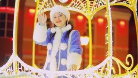 Ένα χαμογελώντας κορίτσι χιονιού που κυματίζει έναν χαιρετισμό από το παράθυρο που λάμπει με τα φω'τα μιας μεταφοράς φιλμ μικρού μήκους