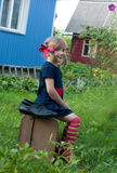 Ένα χαμογελώντας μικρό κορίτσι που παρουσιάζει Pippi Longstocking και που κάθεται σε μια παλαιά βαλίτσα κοντά σε ένα εξοχικό σπίτ Στοκ Εικόνες