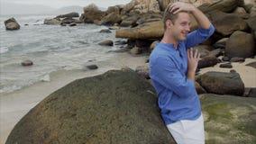 Ένα χαμογελώντας ξανθό άτομο σε ένα μπλε πουκάμισο στέκεται στην παραλία κοντά στις μεγάλες πέτρες και ισιώνει την τρίχα του απόθεμα βίντεο