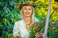 Ένα χαμογελώντας όμορφο κορίτσι με τα συμπαθητικά λουλούδια Στοκ Εικόνα