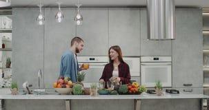 Ένα χαρισματικό νέο ζεύγος που κάνει το καταφερτζή μαζί στη σύγχρονη κουζίνα, μπροστά από το camere, την κυρία προετοιμάζεται απόθεμα βίντεο