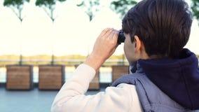 Ένα χαριτωμένο αγόρι εξετάζει τη γειτονιά μέσω των διοπτρών απόθεμα βίντεο