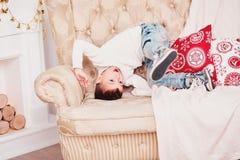 Ένα χαριτωμένο αγόρι πέφτει στον καναπέ Ένας φίλαθλος τύπος σε ένα άσπρο πλεκτό πουλόβερ και τα τζιν και ένα μοντέρνο hairdo κάνο Στοκ Φωτογραφίες