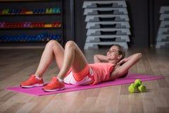 Ένα χαριτωμένο αθλητικό exersice άσκησης γυναικών σε ένα υπόβαθρο γυμναστικής Ένα όμορφο κορίτσι λικνίζει τον Τύπο σε μια γυμναστ Στοκ Φωτογραφία