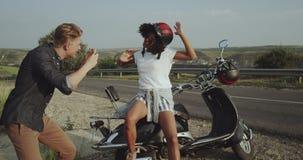 Ένα χαριτωμένο ζεύγος είναι κοντά στο δρόμο και αγκαλιάζει και εξετάζει το ηλιοβασίλεμα απόθεμα βίντεο