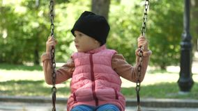Ένα χαριτωμένο κορίτσι για τέσσερα χρονών οδηγά σε μια ταλάντευση μια όμορφη ηλιόλουστη ημέρα φθινοπώρου στο πάρκο Οικογενειακή η απόθεμα βίντεο