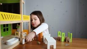 Ένα χαριτωμένο κορίτσι που παίζει με ένα dollhouse φιλμ μικρού μήκους