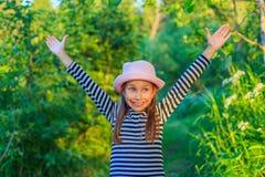 Ένα χαριτωμένο μικρό ευτυχές κορίτσι στο δάσος μια ηλιόλουστη θερινή ημέρα στοκ εικόνες