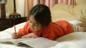 Ένα χαριτωμένο μικρό ισπανικό παιδί που βρίσκεται στο κρεβάτι που χρωματίζει ήσυχα απόθεμα βίντεο