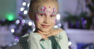 Ένα χαριτωμένο μικρό κορίτσι με τη φωτεινή σύνθεση εξετάζει τη κάμερα και χαμογελά απόθεμα βίντεο