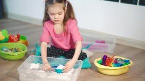 Ένα χαριτωμένο μικρό κορίτσι που παίζει με την κινητική άμμο στο σπίτι απόθεμα βίντεο