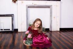 Ένα χαριτωμένο μικρό κορίτσι σε ένα φόρεμα κάθεται στο πάτωμα με αυξήθηκε σε μια φιάλη Εξέταση τη κάμερα o Γλυκιά πριγκήπισσα Θόρ στοκ φωτογραφία με δικαίωμα ελεύθερης χρήσης
