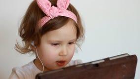 Ένα χαριτωμένο μικρό κορίτσι φυλλομετρεί ένα playlist στην ταμπλέτα, επιλογές και ακούει το τραγούδι στα ακουστικά Αστείο παιδί μ απόθεμα βίντεο