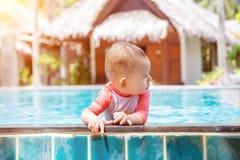 Ένα χαριτωμένο μικρό μωρό προσκολλάται στην πλευρά της λίμνης έξω και κοιτάζει στο δικαίωμα Το κορίτσι νηπίων κολυμπά στο θερινό  στοκ εικόνα