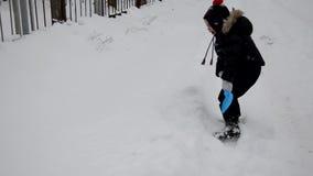 Ένα χαριτωμένο μικρό παιδί ρίχνει το χιόνι στο χειμερινό χιονισμένο δάσος, δέντρα στο χιόνι απολαμβάνει το χειμώνα χιονιές παιχνι φιλμ μικρού μήκους