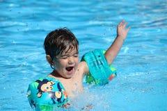 Ένα χαριτωμένο μικρό παιδί στα διογκώσιμα μανίκια που απολαμβάνει το χρόνο του σε μια πισίνα κατά τη διάρκεια ενός καυτού θερινού Στοκ Εικόνες